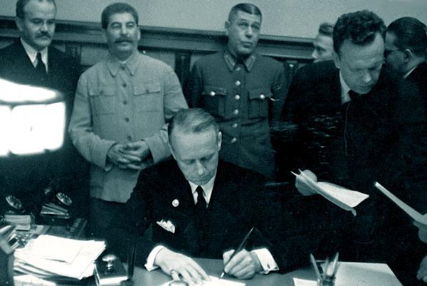 Молотов подписывает договор, Сталин сзади