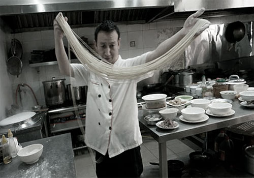 Китайский повар готовит лапшу рамен