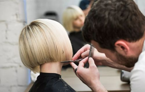 Подстригает волосы девушке